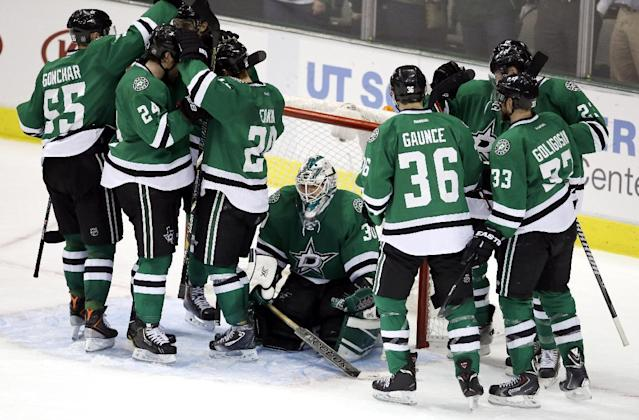 The Dallas Stars surround goalie Dan Ellis, center, as they celebrate the team's 3-2 win over the Colorado Avalanche in an NHL hockey game, Tuesday, Dec. 17, 2013, in Dallas. (AP Photo/Tony Gutierrez)