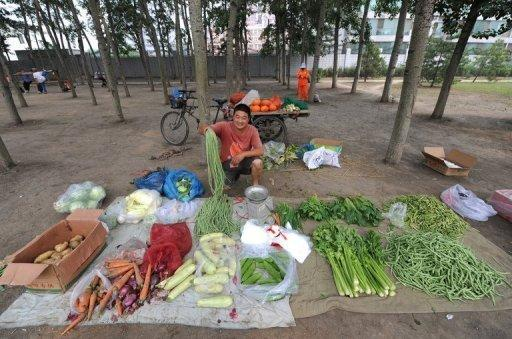 A vendor arranges vegetables in Beijing, on Monday. China's inflation rate slowed to 2.2% in June, official data showed on Monday, giving the government further room to move as it seeks to reignite growth in the world's second biggest economy