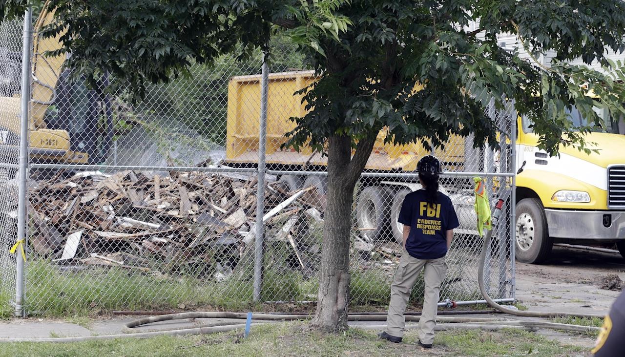 "An FBI agent watches as the house where three women were held captive and raped for more than a decade is being demolished Wednesday, Aug. 7, 2013, in Cleveland. Authorities want to make sure the rubble isn't sold online as ""murderabilia,"" though no one died there. The house was torn down as part of a deal that spared Ariel Castro a possible death sentence. He was sentenced last week to life in prison plus 1,000 years. Castro apologized but blamed his addiction to pornography. (AP Photo/Tony Dejak)"