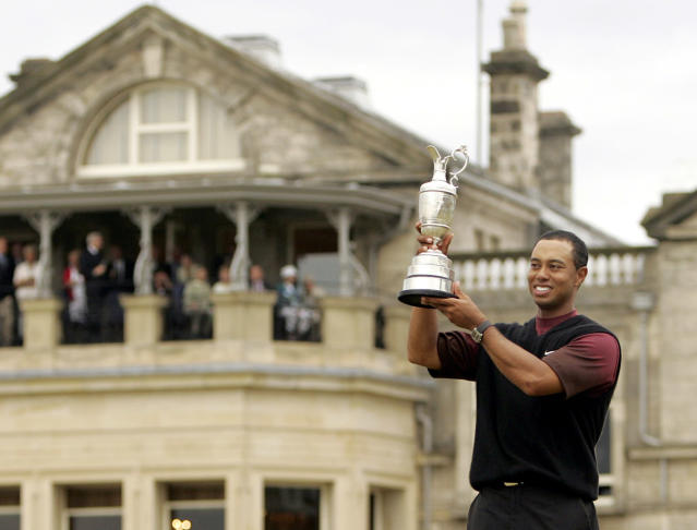 FILE - A July 17, 2005, file photo, Tiger Woods, of the United States, holds up the Claret Jub as he stands in front of the clubhouse after winning the British Open golf championship on the Old Course at St. Andrews, Scotland. (AP Photo/Alastair Grant, File)