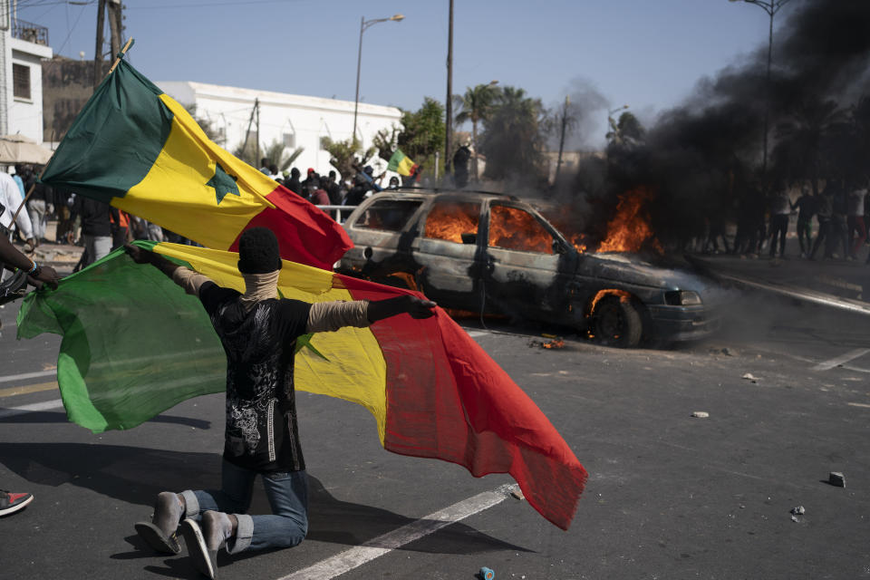 A demonstrator holds a Senegalese flag as he kneels in front of a burning car during protests against the arrest of opposition leader and former presidential candidate Ousmane Sonko, Senegal, Monday, March 8, 2021. Senegalese authorities have freed opposition leader Ousmane Sonko while he awaits trial on charges of rape and making death threats. The case already has sparked deadly protests threatening to erode Senegal's reputation as one of West Africa's most stable democracies. That's because Sonko's supporters are accusing President Macky Sall of pursuing the criminal charges to derail the opposition figure's prospects in the upcoming 2024 election. (AP Photo/Leo Correa)