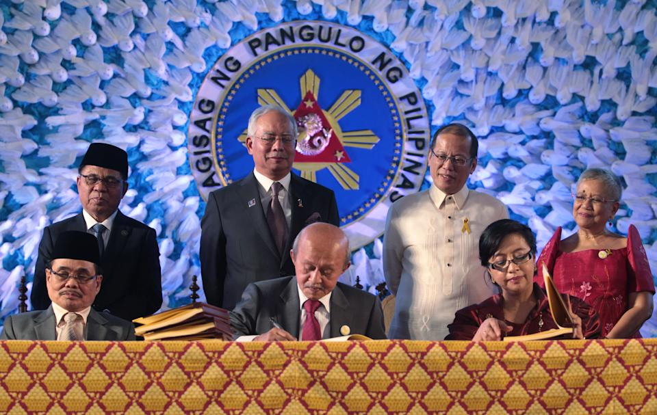 FILE PHOTO:  In this handout from the Presidential Photo Division, President Benigno S. Aquino III and Malaysian Prime Minister Dato' Sri Haji Mohammad Najib bin Tun Haji Abdul Razak witness Moro Islamic Liberation Front Peace Panel chairman Mohagher Iqbal GPH Peace Panel chairperson Professor Miriam Coronel-Ferrer and Malaysian facilitator Tengku Dato Abdul Ghafar sign the Comprehensive Agreement on the Bangsamoro (CAB) in a ceremony at the Kalayaan Grounds of the Malacañan Palace. The agreement effectively ends four decades of deadly fighting between the Philippine government and the largest Muslim insurgency in the troubled southern island of Mindanao which has claimed around 150,000 casualties on both sides and displaced tens of thousands. The historic agreement grants local autonomy and self governance in regional areas the Muslims regard as their ancestral homeland.  (Photo by Presidential Photo Division via Getty Images)