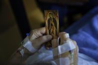 A patient holds an Our Lady of Guadalupe card in his bed while talking to chaplain Nancy Many at Providence Holy Cross Medical Center in the Mission Hills section of Los Angeles on Saturday, Jan. 9, 2021. As families are barred from visiting loved ones to curb the disease's spread, chaplains often are there to act as surrogates, holding the hands of the dying, praying with them and carrying iPads into hospital rooms to provide a real-time connection with grieving families. (AP Photo/Jae C. Hong)