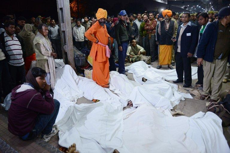 Officials stand among some of the travellers that were killed during a stampede at the railway station in Allahabad, on February 10, 2013. At least 36 people died in a terrifying stampede as pilgrims headed home from India's Kumbh Mela religious festival, which drew a record 30 million people to the banks of the Ganges