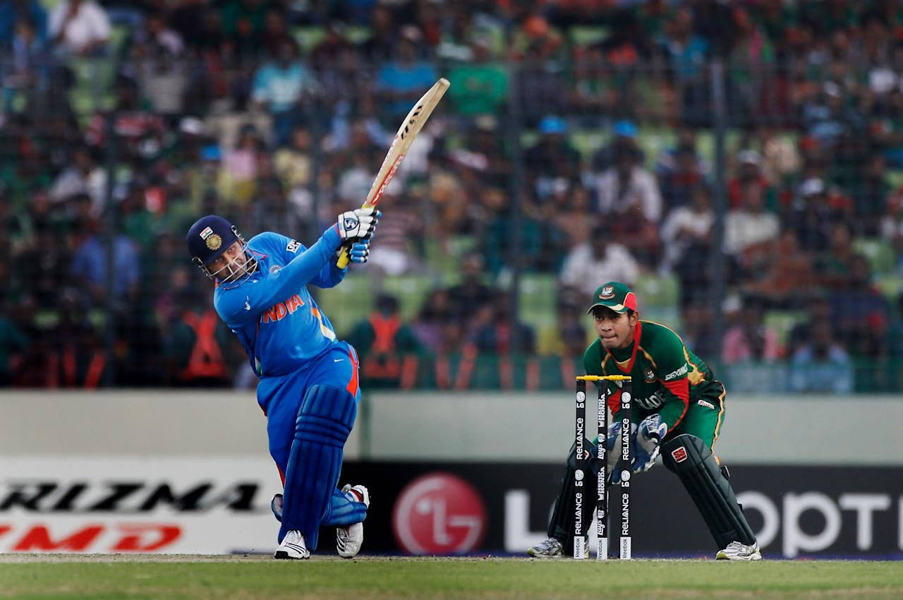 DHAKA, BANGLADESH - FEBRUARY 19:  Virender Sehwag of India hits a six as wicketkeeper Mushfiqur Rahim of Bangladesh looks on during the opening game of the ICC Cricket World Cup between Bangladesh and India at the Shere-e-Bangla National Stadium on February 19, 2011 in Dhaka, Bangladesh.  (Photo by Daniel Berehulak/Getty Images)