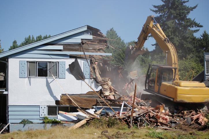 An excavator demolishing a white house.