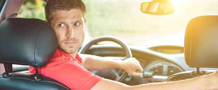 Handsome man driver looking back and parking car
