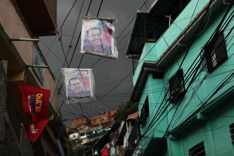 Posters of Venezuela's President Hugo Chavez hang over a street in the Petare neighborhood of Caracas, Venezuela, Friday, Oct. 5, 2012. The last time he ran for re-election, Chavez won comfortably in Petare, one of Latin America's biggest slums with nearly half a million people. This time around, as Venezuelans vote Sunday, he may not. The neighborhood is divided, owing in some degree to mismanagement by pro-Chavez mayors and governors who were voted out of office in 2008 and 2010, respectively. (AP Photo/Rodrigo Abd)