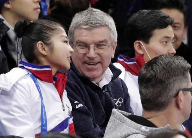 IOC President Thomas Bach, centre, talks to North Korean figure skater Ryom Tae Ok, left, and Kim Ju Sik, right, as they watch the pairs free skate figure skating final in the Gangneung Ice Arena at the 2018 Winter Olympics in Gangneung, South Korea, Thursday, Feb. 15, 2018. (AP Photo/Julie Jacobson)