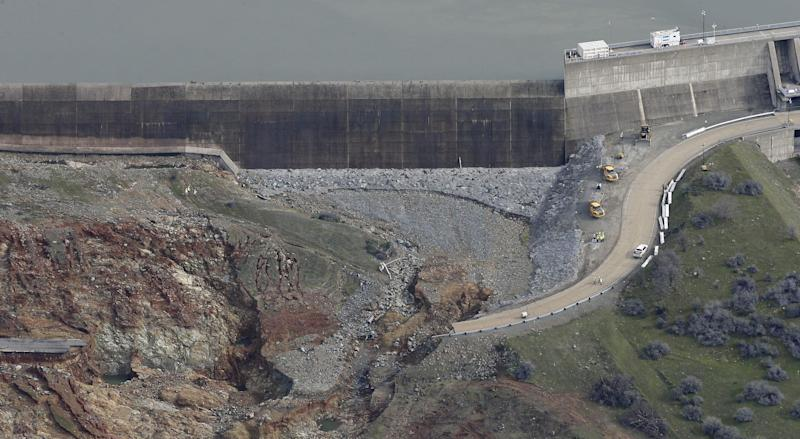 FILE--This Feb. 13, 2017, file photo, shows erosion caused when overflow water cascaded down the emergency spillway, right, of the Oroville Dam in Oroville, Calif. The bill to repair California's roadways hammered by floods and rockslides in an onslaught of storms this winter is already at least $550 million, more than double what the state budgeted for such emergencies. (AP Photo/Rich Pedroncelli, file)