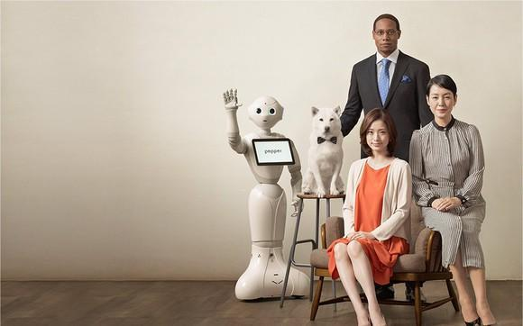 Softbank's iconic Pepper robot standing with people and a dog