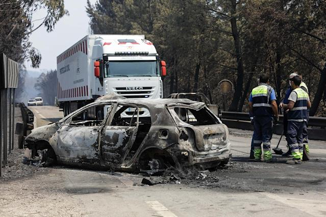 <p>A Portuguese Civil Protection refrigerated truck arrives to transport the bodies of victims near burned cars on a road between Figueiro dos Vinhos and Castanheira de Pera, Pedrogao Grande, central Portugal, June 18, 2017. At least 62 people have been killed in forest fires in central Portugal, many of them trapped in their cars as flames swept over a road Saturday evening. (Paulo Novais/EPA/Rex/Shutterstock) </p>