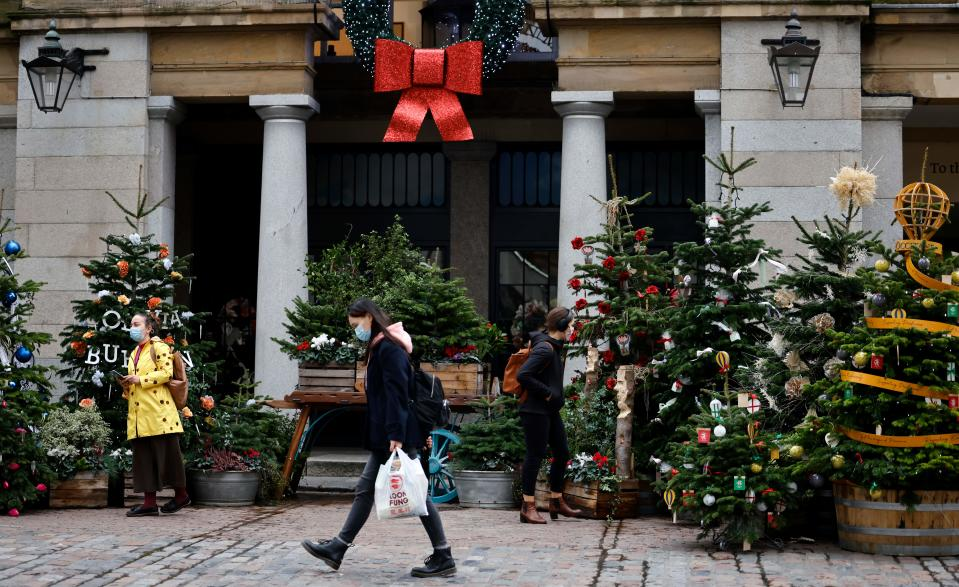 Pedestrians wearing face masks or coverings due to the COVID-19 pandemic, walk past Christmas trees in Covent Garden in central London on November 17, 2020. - Britain has been the worst-hit nation in Europe recording more than 50,000 coronavirus deaths from some 1.2 million positive cases. (Photo by Tolga Akmen / AFP) (Photo by TOLGA AKMEN/AFP via Getty Images)