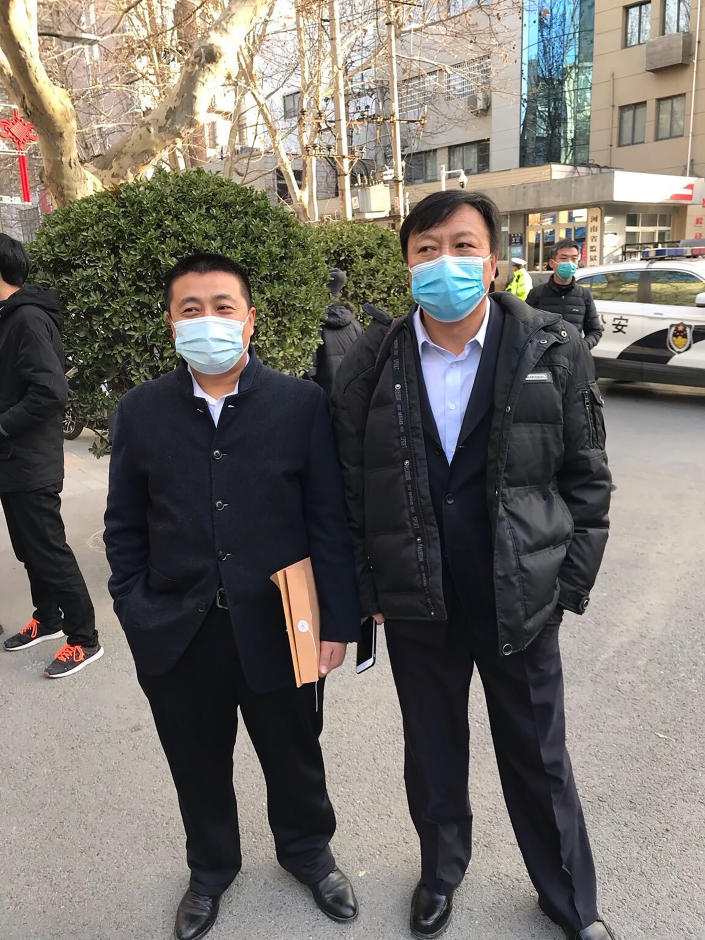 In this photo provided to the Associated Press, Chinese lawyer Ren Quanniu, left, stands with his attorney Bao Longjun outside the Henan provincial Justice Department's office in Zhengzhou in central China's Henan Province, Friday, Jan. 29, 2021. A second Chinese lawyer who represented a Hong Kong pro-democracy activist has been stripped of his license as Beijing attempts to crush opposition to its tighter control over the territory. (AP Photo)