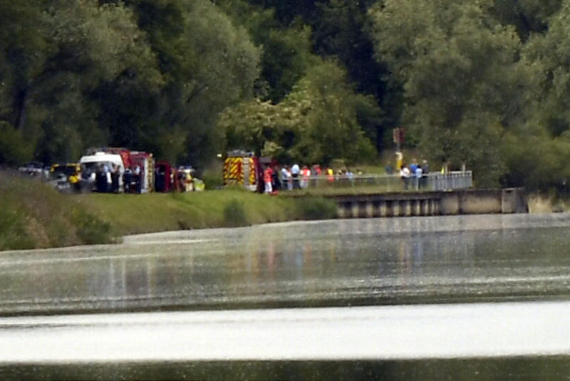 Rescue vehicles and police officers gather near Gerstheim, eastern France, Thursday, May 30, 2019. Police say three people were killed and a child disappeared after a small boat capsized in the Rhine River between Germany and France. (AP Photo)