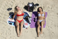 Sorrell Vince, 23, left, from Northampton and Bethany Heatley from Preston enjoying the sun on Cullercoats Beach, in Tynemouth, England, Wednesday May 20, 2020. Lockdown restrictions due to the coronavirus outbreak have been relaxed allowing unlimited outdoor exercise and activities such as sunbathing. The Met Office has predicted the hottest day of the year so far with temperatures set to hit 28C (82.4F). (Owen Humphreys/PA via AP)