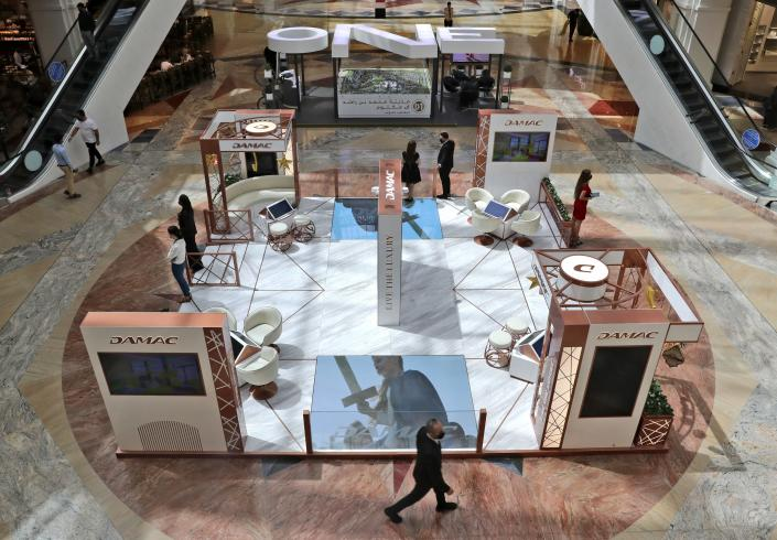 Sales people from two major real estate developers wait for customers at their shopping mall stands, in Dubai, United Arab Emirates, Wednesday, May 5, 2021. Foreign buyers flush with cash have flooded the high-end property market in Dubai even as coronavirus vaccines roll out unevenly across the world and waves of infections force countries to extend restrictions. It's one of the few places in the world where they can dine, shop and do business in person. (AP Photo/Kamran Jebreili)