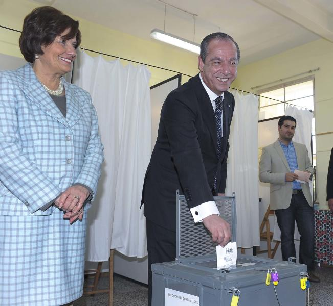 Maltese Prime Minister Lawrence Gonzi smiles for media as he casts his ballot and his wife Catherine Callus looks on, in Valletta, Malta, Saturday, March 9, 2013. Maltese head to the polls Saturday to decide whether to grant the center-right Nationalist Party a fourth straight term or give the opposition a shot at government after 15 years. (AP Photo/Lino Arrigo Azzopardi)