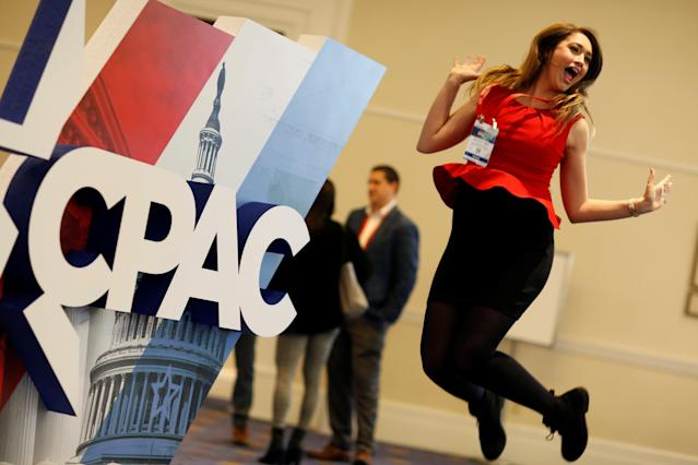 <p>Elizabeth Mills jumps in front of the Conservative Political Action Conference (CPAC) sign at National Harbor, Md., Feb. 23, 2018. (Photo: Joshua Roberts/Reuters) </p>