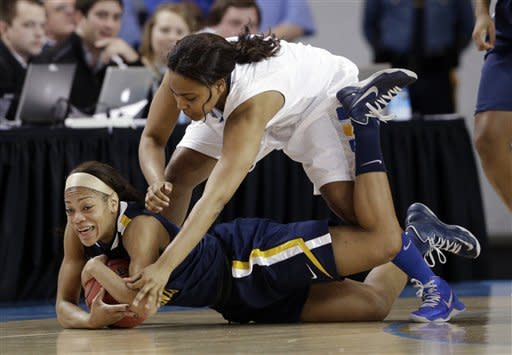 West Virginia guard Christal Caldwell, bottom, tries to protect the ball from Delaware guard Jaquetta May during the first half of a first-round game in the women's NCAA college basketball tournament in Newark, Del., Sunday, March 24, 2013. (AP Photo/Patrick Semansky)