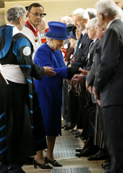 Britain's Queen Elizabeth II, centre, distributes Maundy money during the Maundy service, at Christ Church Cathedral in Oxford, England, Thursday, March 28, 2013. The Queen distributed the Maundy money to 87 women and 87 men, one for each of The Queen's 87 years. Each recipient receives two purses, one red and one white. The red purse will contain a 5 pound coin and 50 pence coin commemorating the 60th anniversary of The Queen's Coronation. The white purse will contain uniquely minted Maundy Money. This takes the form of silver one, two, three and four penny pieces, the sum of which equals the number of years the Monarch has years of age. This year there will be 87 pennies worth distributed. (AP Photo/Kirsty Wigglesworth, Pool)