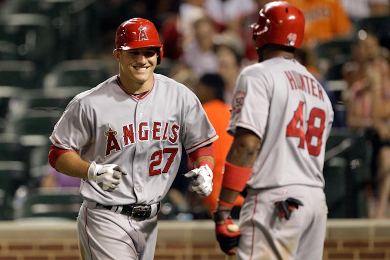 BALTIMORE, MD - JULY 22: Mike Trout #27 celebrates scoring with teammate Torii Hunter #48 of the Los Angeles Angels of Anaheim during the seventh inning against the Baltimore Orioles at Oriole Park at Camden Yards on July 22, 2011 in Baltimore, Maryland. (Photo by Rob Carr/Getty Images)