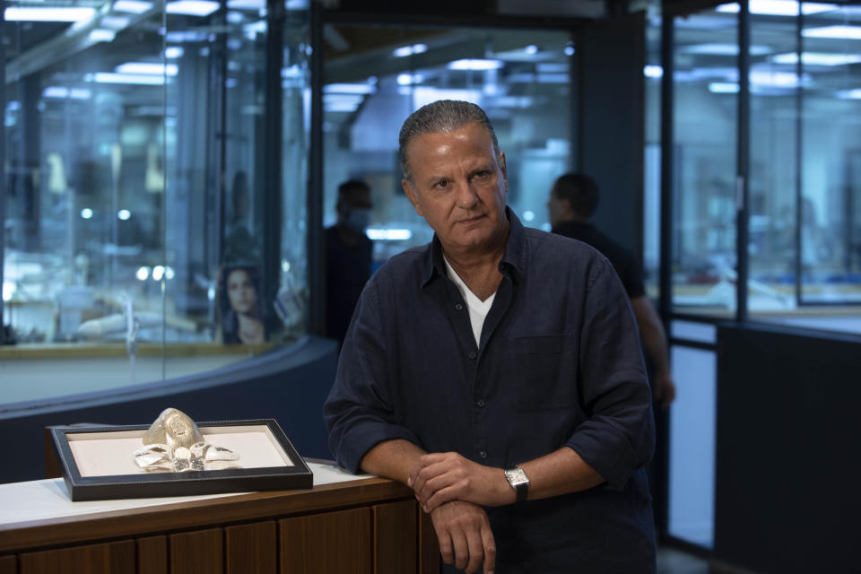 Isaac Levy, owner of Israeli jewelry company Yvel speaks during an interview with the Associated Press next to parts of a mask in Motza near Jerusalem, Sunday, Aug. 9, 2020. An Israeli jewelry company is working on what it says will be the world's most expensive coronavirus mask, a gold, diamond-encrusted face covering with a price tag of $1. 5 million. (AP Photo/Sebastian Scheiner)