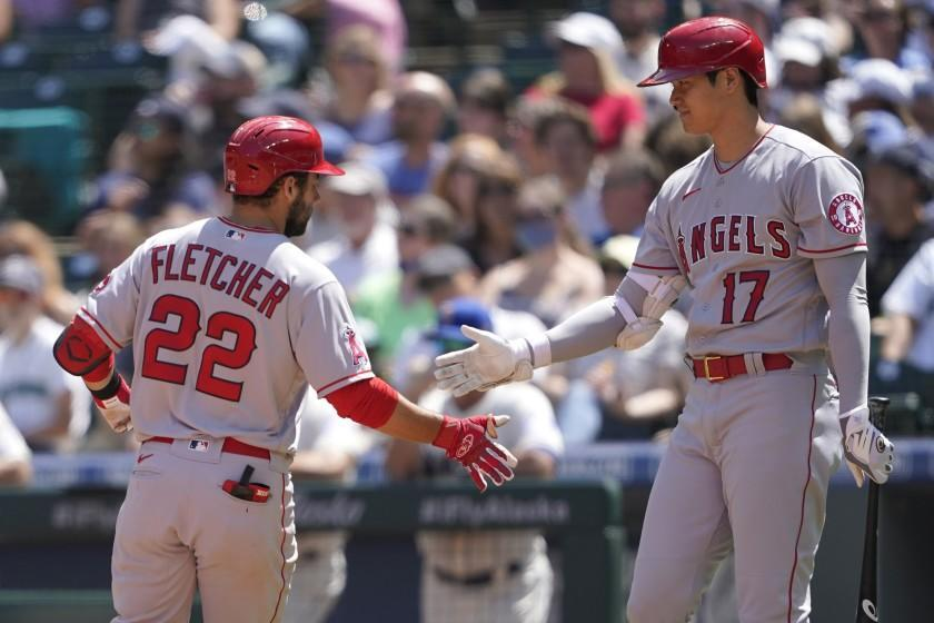 Los Angeles Angels' David Fletcher (22) is greeted at the plate by Shohei Ohtani (17) after Fletcher hit a solo home run during the third inning of a baseball game against the Seattle Mariners, Sunday, July 11, 2021, in Seattle. (AP Photo/Ted S. Warren)