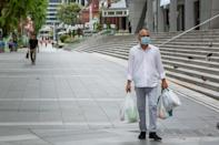 A man in a face mask seen carrying groceries along Orchard Road on 7 April 2020, the first day of Singapore's month-long circuit breaker period. (PHOTO: Dhany Osman / Yahoo News Singapore)