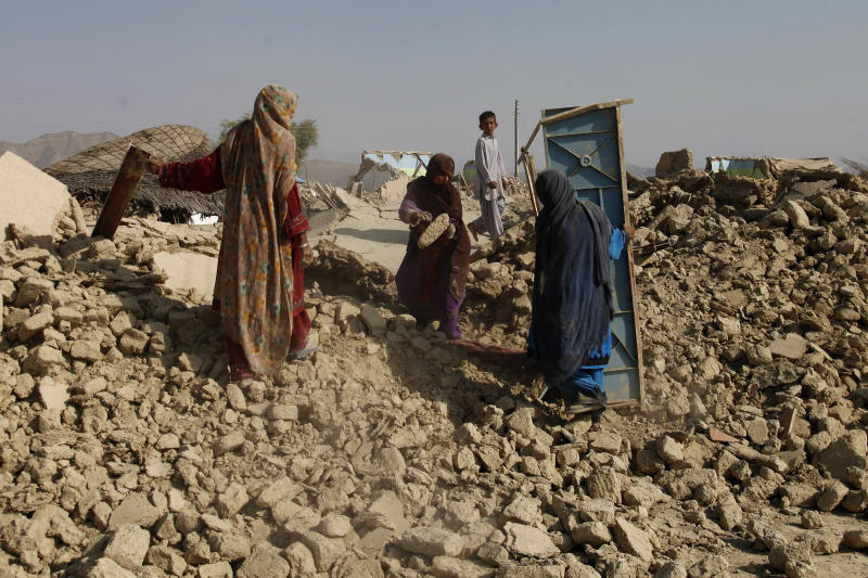 Pakistani women search their belongings through rubble of a house, which was destroyed in Tuesday's earthquake, in the remote district of Awaran in Baluchistan province, Pakistan, Friday, Sept. 27, 2013. Desperate Pakistani villagers in remote areas hit by the massive earthquake this week said they are still waiting for government aid to reach them. (AP Photo/Shakil Adil)