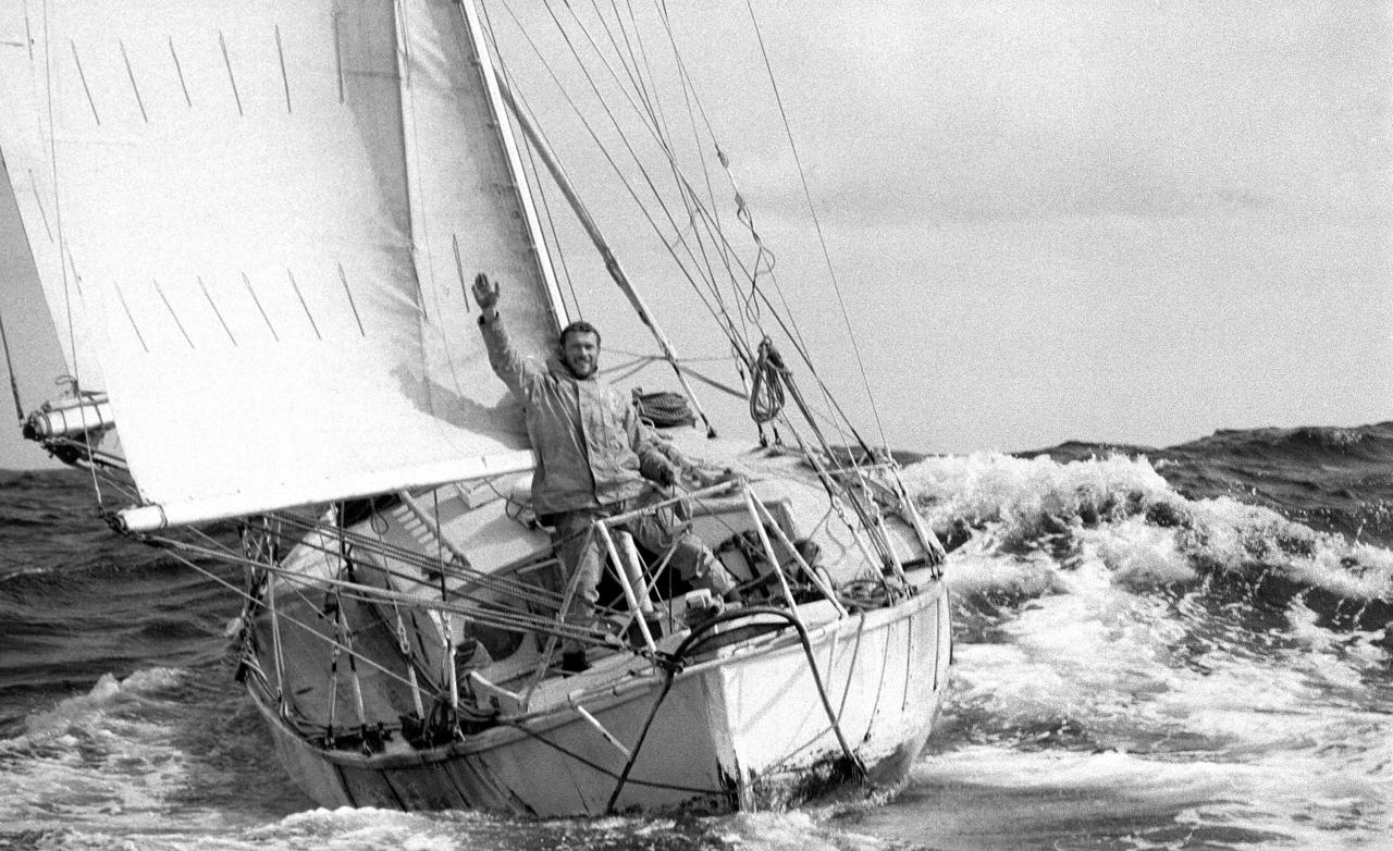 This 1969 photo provided by Bill Rowntree/PPL Media shows Robin Knox-Johnston waving aboard his 32-foot yacht Suhaili off the coast of Falmouth, England, after becoming the first man to sail solo non-stop around the globe. In the spring of 1969, less than three months before man landed on the moon, Knox-Johnston achieved the nautical equivalent of climbing Mount Everest when he became the first man to sail alone around the world nonstop. GPS hadn't been invented, so the veteran of the British merchant navy made his way around the globe the old-fashioned way, with a sextant. (Bill Rowntree/PPL Media via AP)