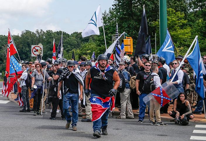 Multiple white nationalist groups march to McIntire Park in Charlottesville, Va., on Aug. 12, 2017. In the center background is a black-and-white American flag with a thin blue line across its center.