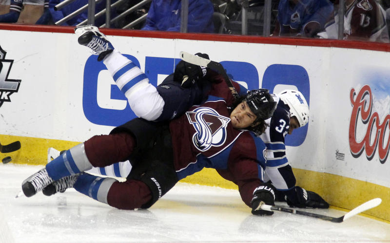 Colorado Avalanche right wing Steve Downie, front, gets tangled up with Winnipeg Jets defenseman Dustin Byfuglien while fighting for control of the puck in the second period of an NHL hockey game in Denver on Sunday, Oct. 27, 2013. (AP Photo/David Zalubowski)