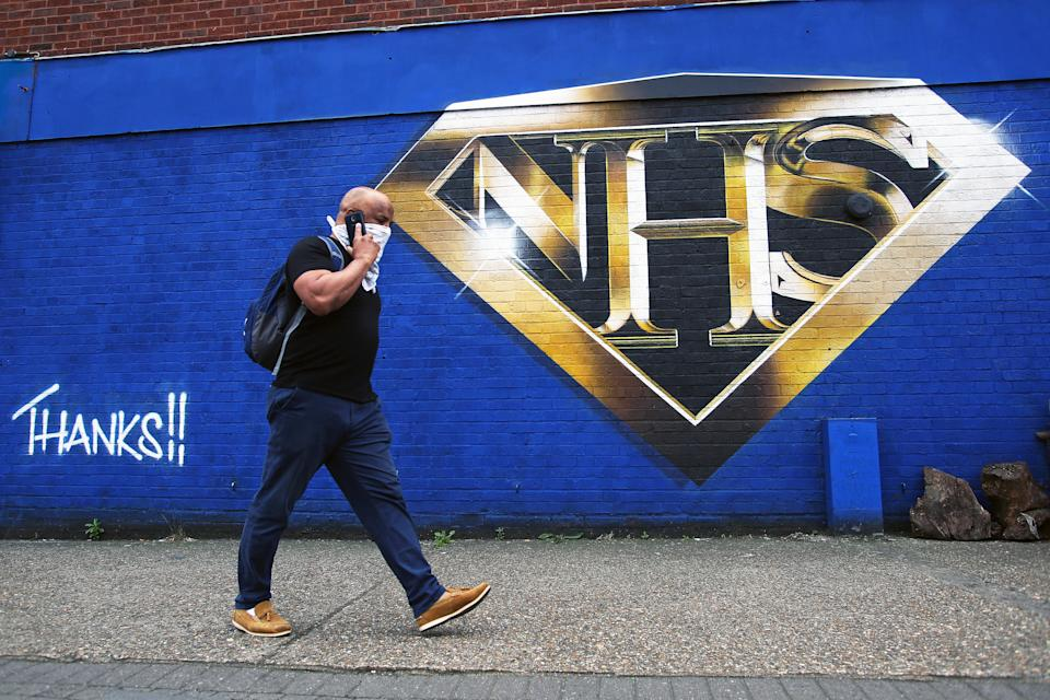 A man walks past an NHS superman graffiti that pays tribute to NHS workers on a wall in Tulse Hill, London, as the UK continues to recover from the coronavirus pandemic.