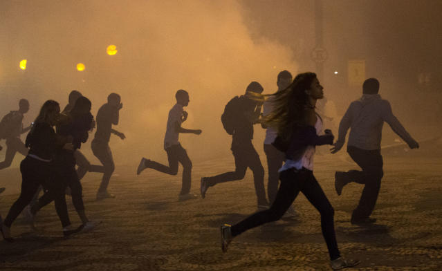 Protesters run from the clouds of tear gas during an anti-government protest in Rio de Janeiro, Brazil, Thursday, June 20, 2013. Police and protesters fought in the streets into the early hours Friday in the biggest demonstrations yet against a government viewed as corrupt at all levels and unresponsive to its people. (AP Photo/Victor R. Caivano)