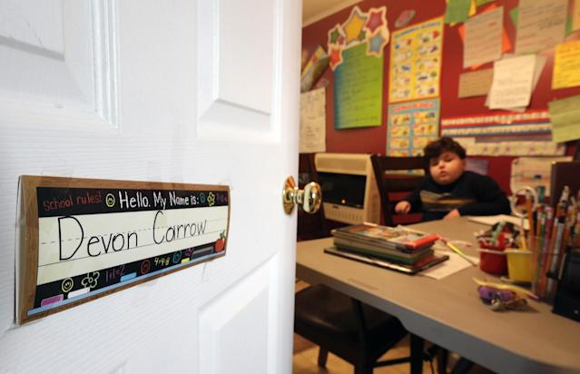 In this Tuesday, Jan. 22, 2013 photo, Devon Carrow attends school from home while operating a robot in the classroom, in Orchard Park N.Y. Carrow's life-threatening allergies don't allow him to go to school. But the 4-foot-tall robot with a wireless video hookup gives him the school experience remotely. (AP Photo/David Duprey)