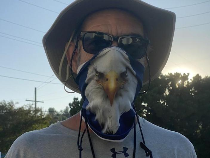 Chaminade football coach Ed Croson wears his Eagles mask while directing his team through a conditioning program.