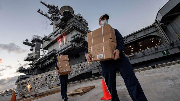 FILE PHOTO: U.S. Navy sailors assigned to the aircraft carrier USS Theodore Roosevelt move ready-to-eat meals (MREs) for quarantined sailors at Naval Base Guam on April 7, 2020. (Us Navy/via Reuters)