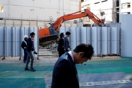 Businessmen walk past heavy machinery at a construction site in Tokyo's business district