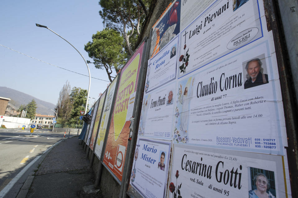 FILE - In this Tuesday, March 17, 2020 filer, death notices are seen on a board along an empty road in Alzano Lombardo, near Bergamo, the heart of the hardest-hit province in Italy's hardest-hit region of Lombardy, Italy, Tuesday, March 17, 2020. As Italy prepares to emerge from the West's first and most extensive coronavirus lockdown, it is increasingly becoming apparent that something went terribly wrong in Lombardy, the hardest-hit region in Europe's hardest-hit country. Two days after Italy registered its first positive case in the Lombard town of Codogno, sparking a lockdown of Codogno and nine nearby towns, another positive case was registered Feb. 23 more than an hour's drive away in the hospital of Alzano Lombardo in the province of Bergamo. Whereas the emergency room of Codogno's hospital was shuttered after its first positive case, the ER of Alzano's hospital reopened after a few hours of cleaning, fast becoming one of Bergamo's main sources of contagion. (AP Photo/Luca Bruno, File)