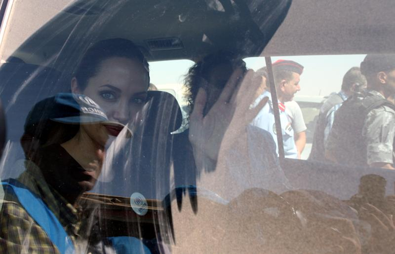 "The U.N. refugee agency's special envoy, actress Angelina Jolie, waves through the dusty window of her car as she departs the Zaatari Refugees Camp in Jordan for Syrians who fled the civil war in their country, Tuesday, Sept. 11, 2012. Jolie said Tuesday she heard ""horrific"" and ""heartbreaking"" accounts from Syrian refugees in a camp which hosts about 30,000 Syrians displaced by the 18-month conflict that has so far claimed at least 23,000 lives, according to activists. (AP photo/Mohammad Hannon)"