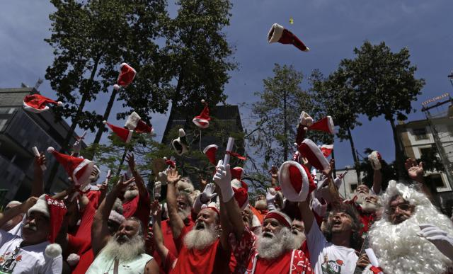 Students from the Brazilian Santa Claus school throw their hats into the air, during their graduation ceremony in Rio de Janeiro, November 12, 2013. The school holds 4 days' lessons in Santa-training, teaching Christmas carols, how to interact with children, and also how to wear the heavy red suit in Rio's typical 104-degree (40 degrees celsius) summer weather that is common around the holidays. REUTERS/Pilar Olivares (BRAZIL - Tags: SOCIETY TPX IMAGES OF THE DAY)