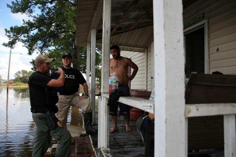 Police speak to a man outside a house surrounded by water in Lumberton, North Carolina