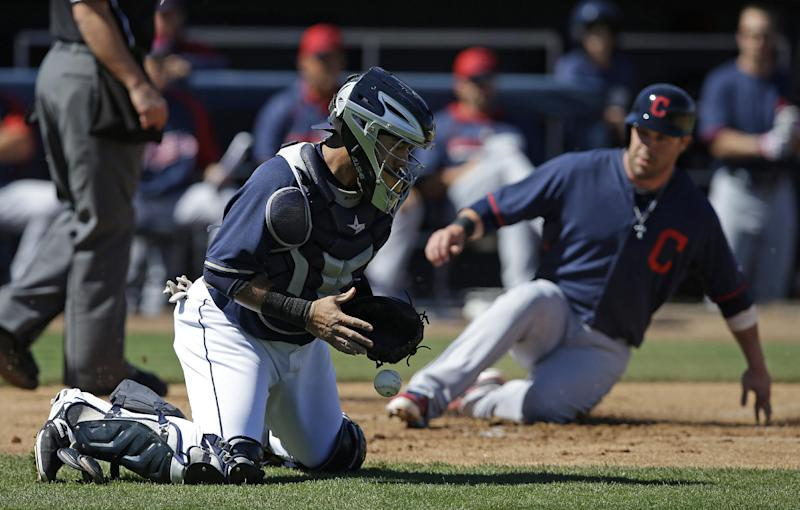 San Diego Padres catcher Rene Rivera (44) blocks a throw as Cleveland Indians' Jason Kipnis scores on a hit by Michael Brantley during the first inning of an exhibition spring training baseball game Saturday, March 8, 2014, in Peoria, Ariz. (AP Photo/Darron Cummings)