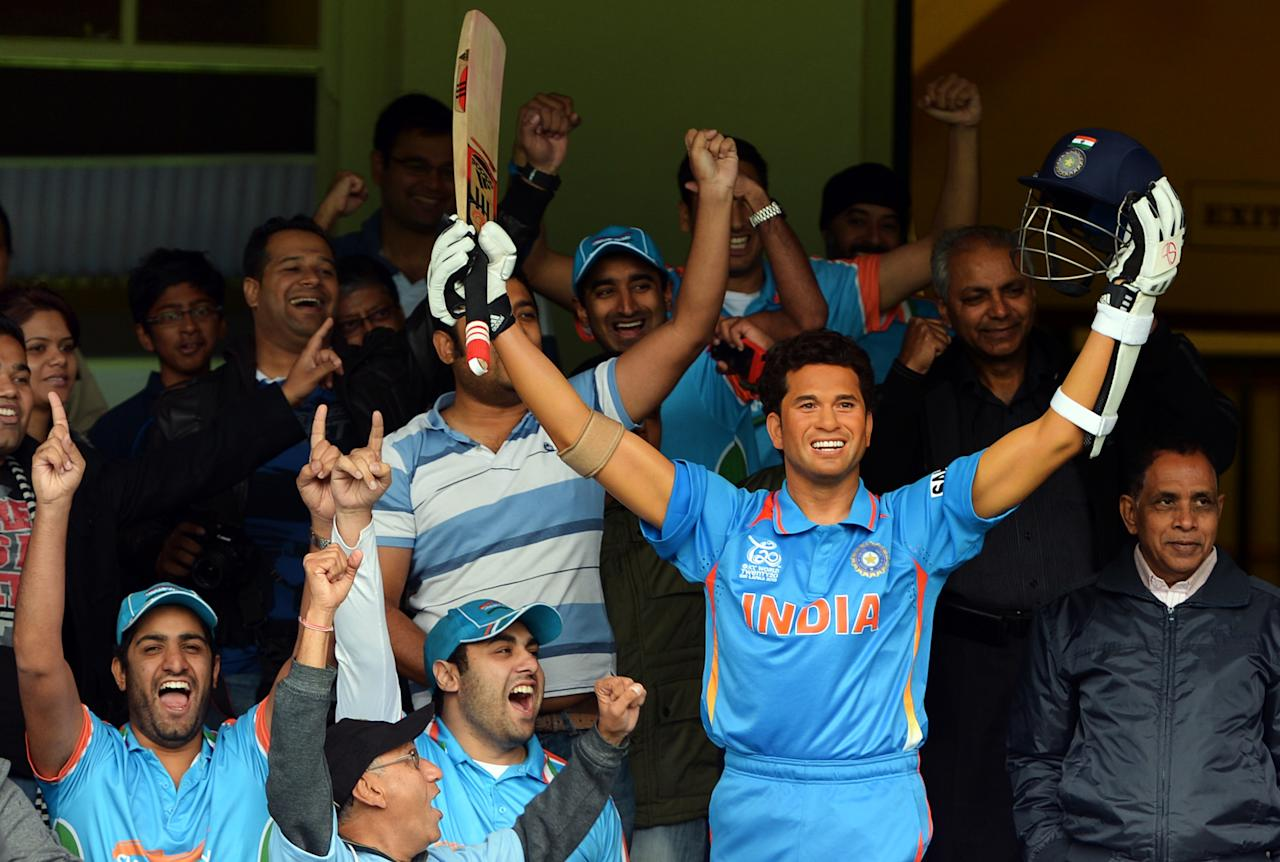 "A group of Indian cricket fans known as the ""Swami Army"" shout slogans next to a wax figure of India's legendry cricket star Sachin Tendulkar, at the Sydney Cricket Ground in Sydney on April 20, 2013. The new wax figure of Tendular will be placed in the sports zone of Madame Tussauds in Sydney.                       AFP PHOTO / Saeed Khan        (Photo credit should read SAEED KHAN/AFP/Getty Images)"