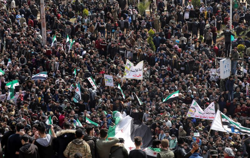 People carry banners and opposition flags during a demonstration in Idlib