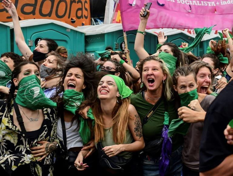 Demonstrators celebrate with green headscarves -- the symbol of abortion rights activists -- outside the Argentine Congress after legislators passed a bill to legalize abortion on December 11