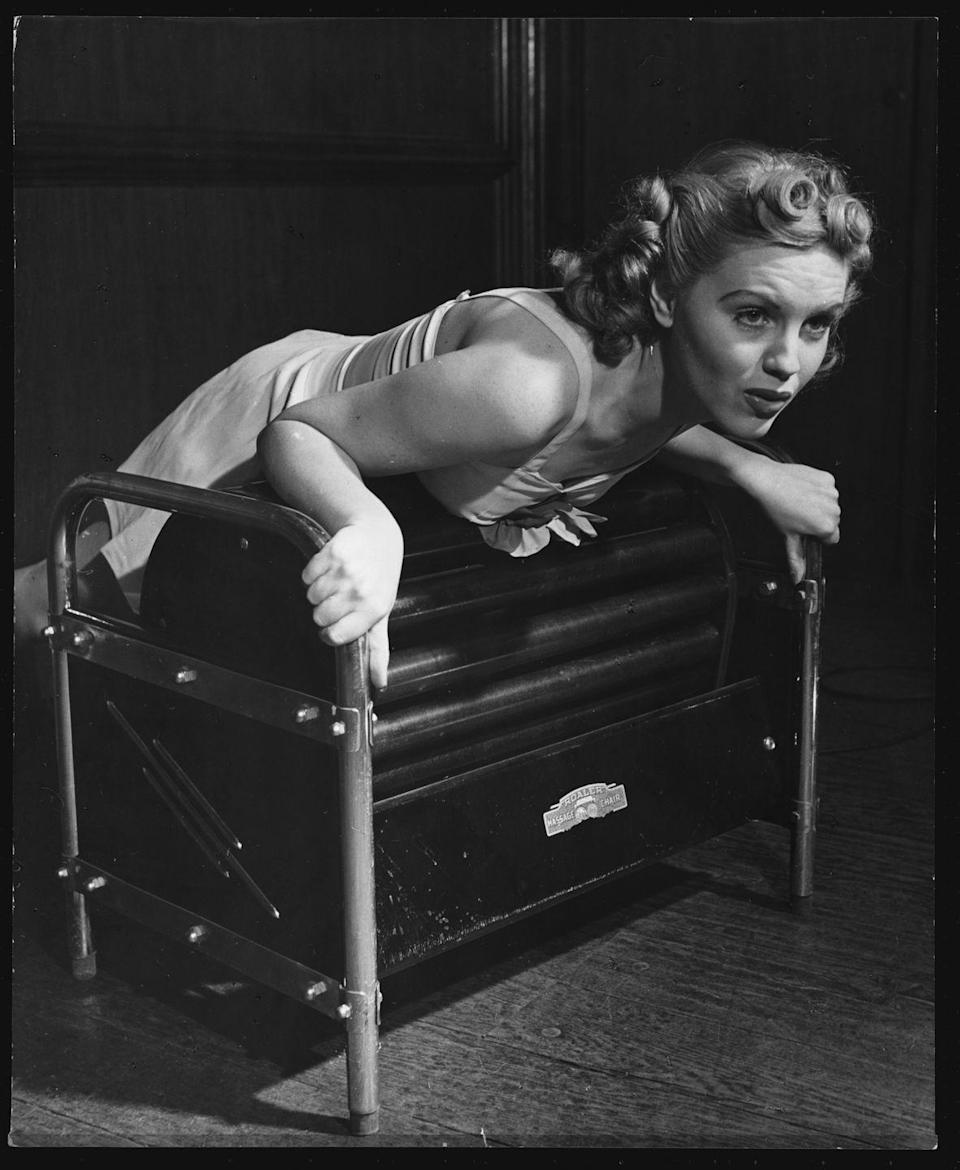 <p>Women were still wearing dresses to exercise, even in the 1940s. This image shows a woman with perfect hair and makeup, exercising on a workout machine typical of the times in a dress. </p>
