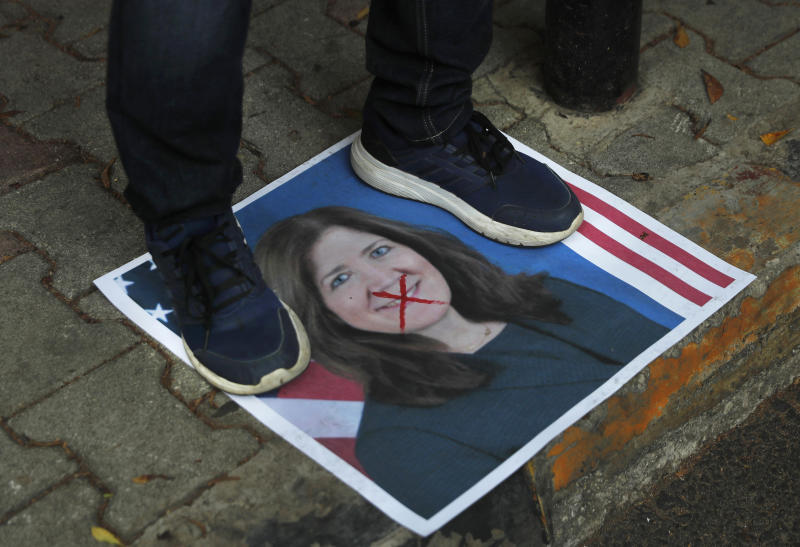 A protester stands on a portrait of the U.S. Ambassador to Lebanon Dorothy Shea, outside the Lebanese Foreign Ministry, in Beirut, Lebanon, Monday, June 29, 2020. Lebanon's foreign minister and the U.S. ambassador to Beirut discussed Monday a court ruling issued over the weekend in which a Lebanese judge banned local and foreign media outlets in the country from interviewing the ambassador for a year over comments she made regarding the powerful Hezbollah group. (AP Photo/Hussein Malla)