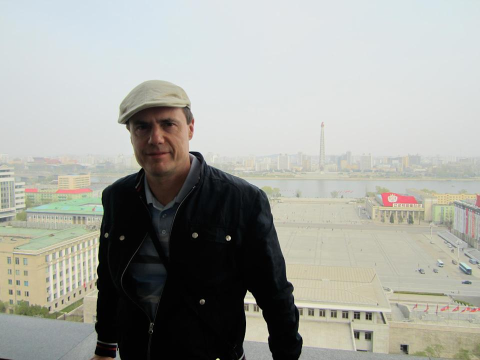 """Me with Kim Il-sung Square in the background, where the regime stages its massive parades. In the far distance is the Juche Tower, which glorifies the regime's official ideology, <em>juche </em>— a baffling hodgepodge of Marxism, Confucianism, and ultranationalism. Our guides become embarrassed when asked to explain it, indicating that it is """"too profound"""" to convey with ease."""